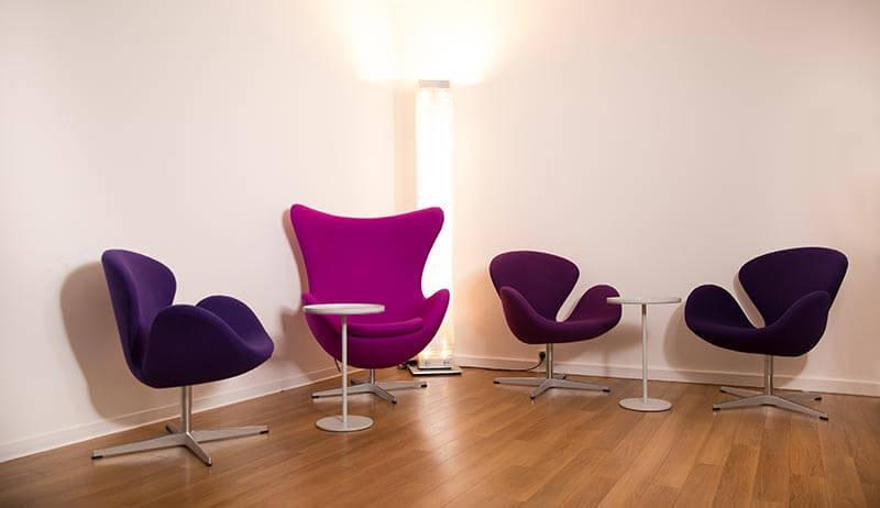 Vier violette Stühle um zwei kleine Tische vor einer weißen Wand