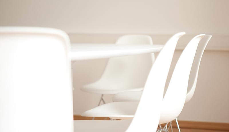 Weiße Stühle an einem weißen Tisch