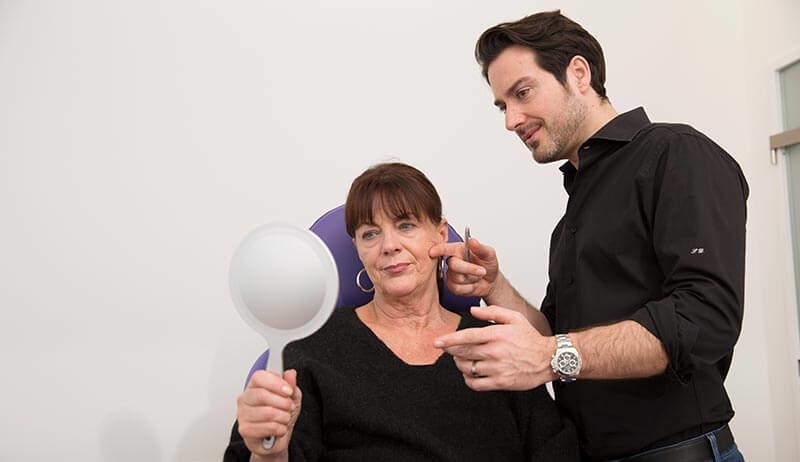 Eine sitzende Frau schaut in einen Handspiegel während ein stehender Mann einen Finger an ihre Wange legt.